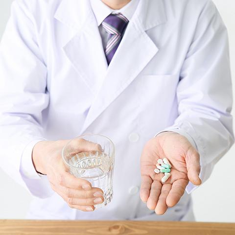 薬を持つ登録販売者の男性